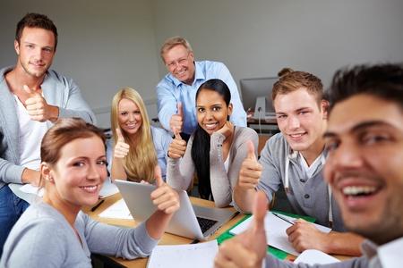 profesor alumno: Estudiantes feliz celebraci�n de los pulgares para arriba en la universidad