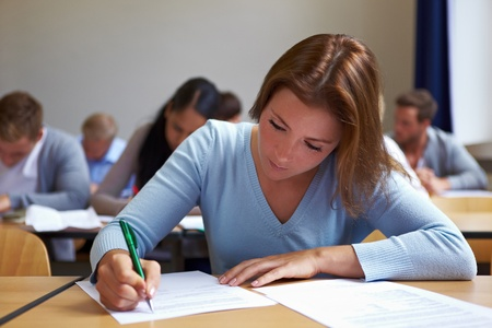 exams: Young woman taking test in job assessment center