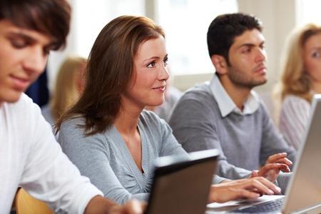 curso de capacitacion: Estudiantes felices con sus computadoras port�tiles en clase de Universidad Foto de archivo