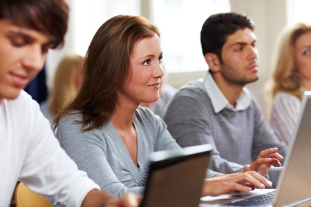 learning online: Happy students with their laptops in university class