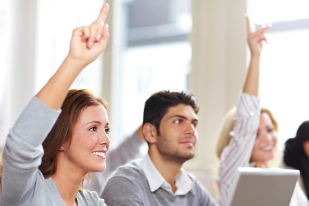 college classroom: Two women raising hands in university class Stock Photo