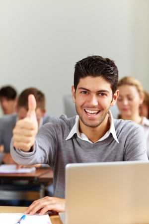 computer lesson: Successful student at laptop holding his thumbs up