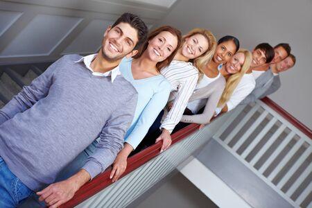 Jonge gelukkige glimlachende tiener mensen in een rij