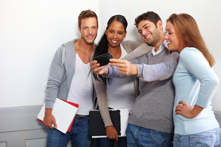 Happy smiling students taking group photos with smartphone