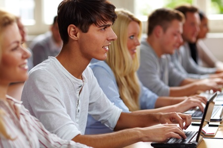school exam: Student using a netbook in university class Stock Photo