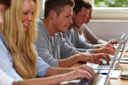Estudiantes felices con sus computadoras port�tiles en clase de Universidad Foto de archivo - 10762988