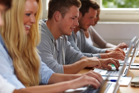 computer lesson: Happy students using their laptops in university class