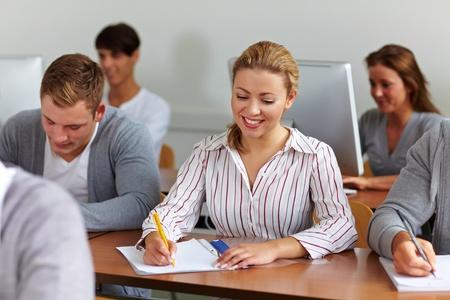 taking note: Felice studentessa universitaria a prendere appunti in classe
