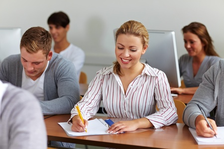 Happy female student taking notes in university class photo