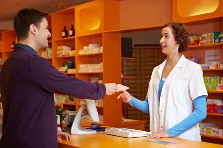 pharmacy technician: Customer in pharmacy giving pharmacist his prescription Stock Photo