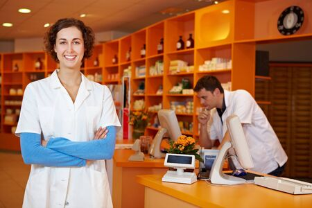 pharmacy technician: Happy pharmacist with arms crossed in her pharmacy Stock Photo