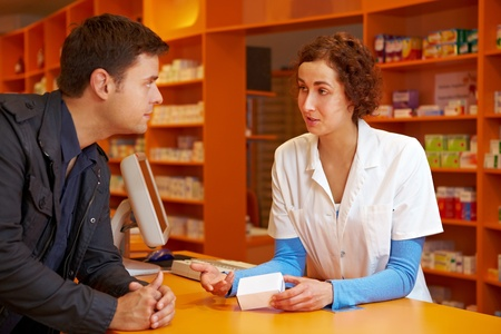 Happy pharmacist talking to customer in a pharmacy photo