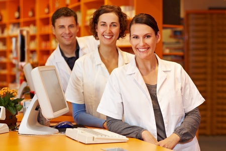 Three pharmacists at a counter in a pharmacy photo
