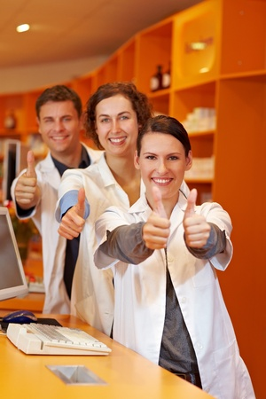 Three successful pharmacists in pharmacy holding thumbs up photo
