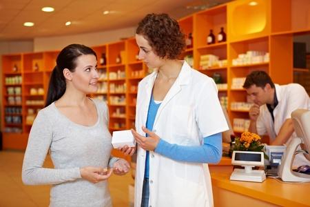 pharmacy technician: Pharmacist talking to woman in a pharmacy