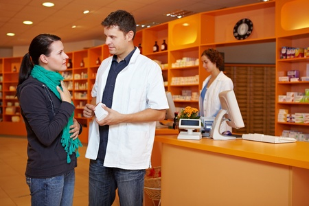 pharmacy technician: Female customer with cold gets advice from pharmacist in pharmacy