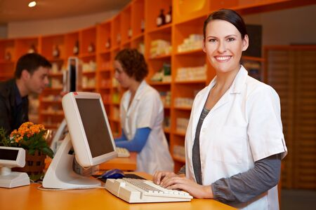 Smiling pharmacist working at computer in a pharmacy photo