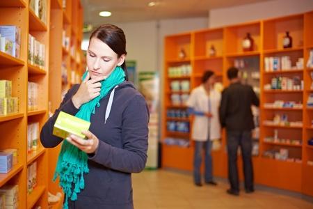 decide: Clienta decide por un producto en una farmacia Foto de archivo