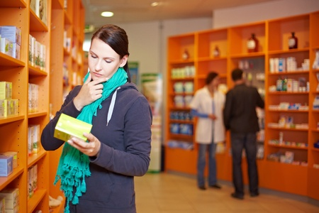 drug store: Female customer decides for a product in a pharmacy