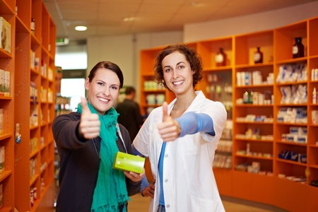 Happy pharmacist and customer holding thumbs up in a pharmacy photo