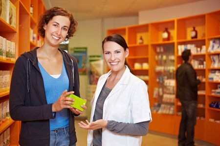 Satisfied female customer with pharmacist in a pharmacy Stock Photo - 10971335