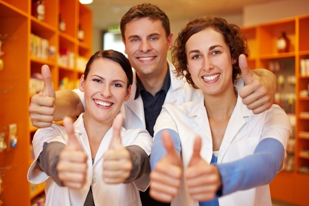 employee satisfaction: Happy pharmacy team holding their thumbs up in a pharmacy Stock Photo