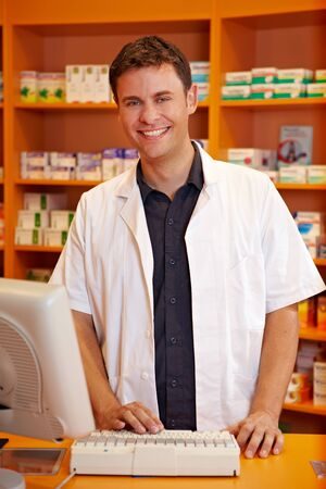 Smiling pharmacist behind the counter of a pharmacy photo
