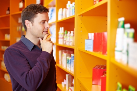 price uncertainty: Pensive man shopping for products in a drugstore