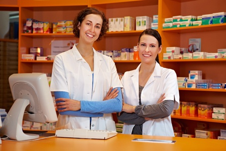 pharmacy technician: Two happy pharmacists with her arms crossed in pharmacy