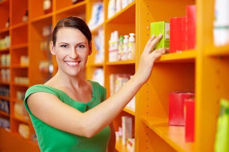 Happy smiling woman shopping for medicine in drugstore photo