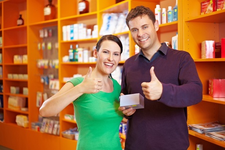 customer services: Happy couple in a pharmacy holding their thumbs up