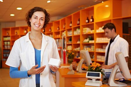 pharmacy technician: Happy pharmacist recommending a drug in a pharmacy Stock Photo