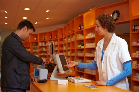 ec: Customer in pharmacy paying with his credit card Stock Photo
