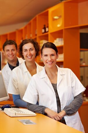 Three happy pharmacists at a counter in a pharmacy photo