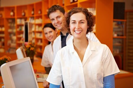 Happy pharmacist with her team in a pharmacy photo