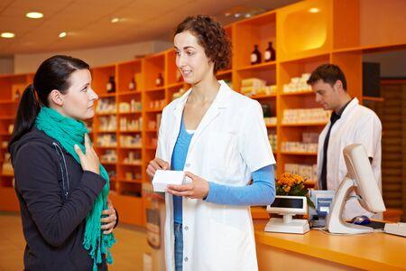 pharmacy technician: Pharmacist recommending medication to female customer in pharmacy