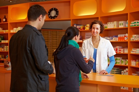 checkout: Two customers Waiting in line in pharmacy for the pharmacist