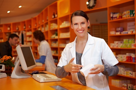 pharmacy technician: Happy pharmacist in pharmacy pointing to medical product