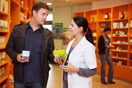 pharmacy technician: Pharmacist talking to a man in a pharmacy Stock Photo
