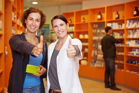 Two happy women in pharmacy holding their thumbs up photo