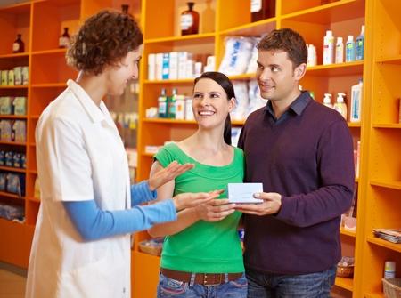 ein: Apothekerin berät ein glückliches Paar in der Apotheke Stock Photo