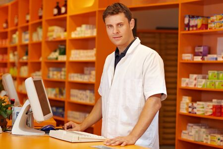 pharmacy technician: Confident pharmacist standing behind counter in a pharmacy