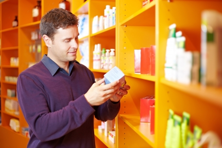 drug store: Critical man checking some products in a pharmacy Stock Photo