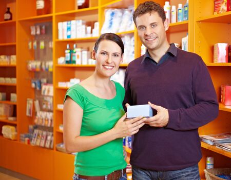Happy couple buying some medicine in a pharmacy photo