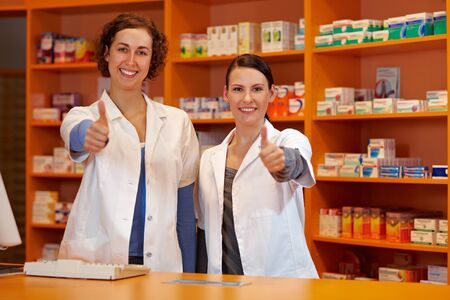 Two happy pharmacists in pharmacy holding their thumbs up photo