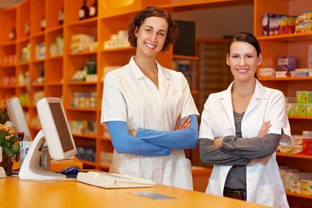 Two confident pharmacists in drugstore with their arms crossed photo