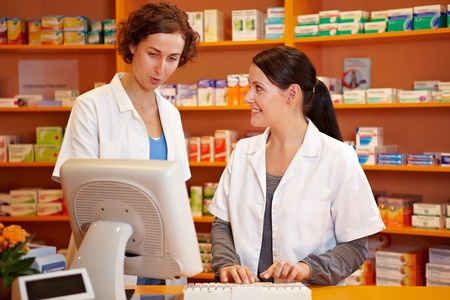 Pharmacist training a pharmacy technician in a drugstore photo