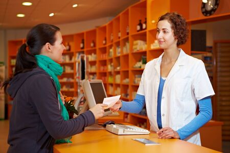 discretion: Customer giving medical prescription to pharmacist in a pharmacy Stock Photo
