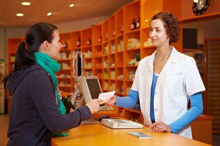 pharmacy technician: Customer giving medical prescription to pharmacist in a pharmacy Stock Photo