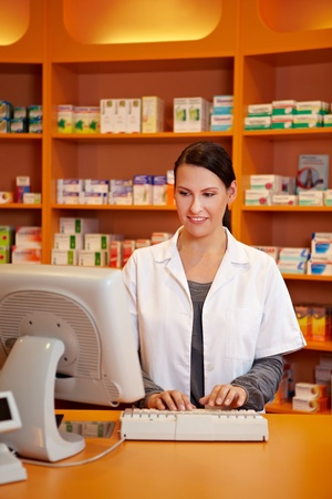 pharmacy technician: Pharmacist ordering medicine with computer in a drugstore Stock Photo